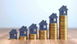 Häuser auf anwachsenden Türmen aus Münzen