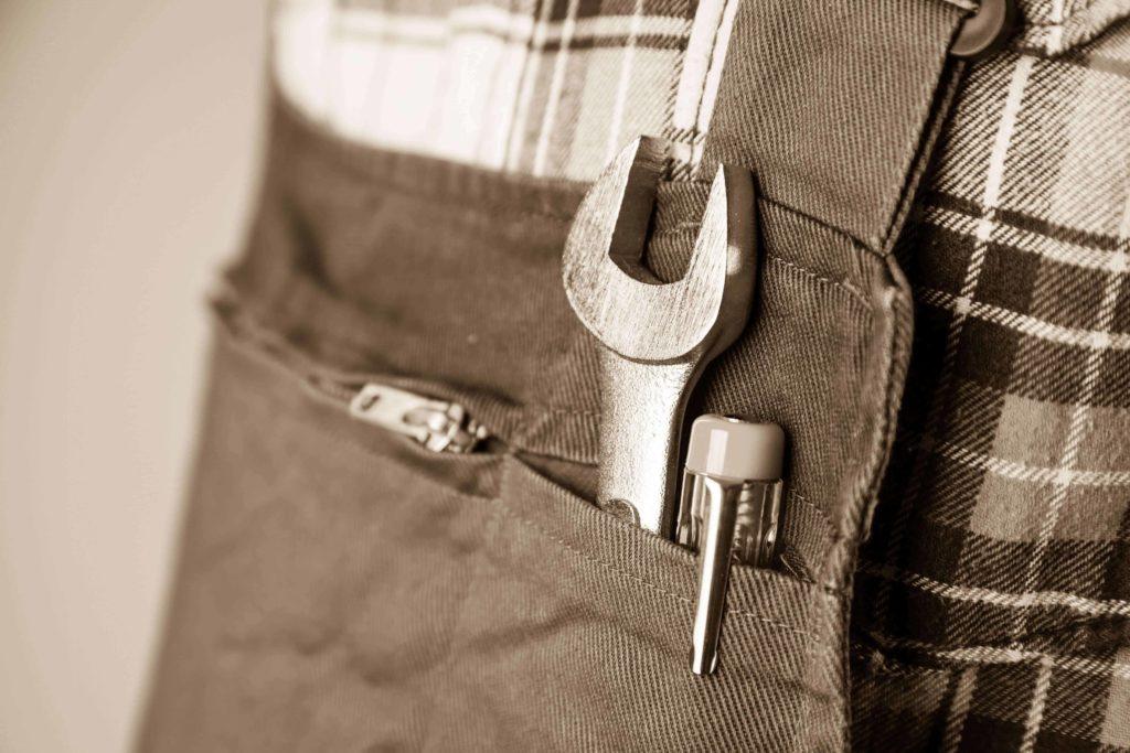 Der Handwerker-Effekt, symbolisiert durch Werkzeuggürtel mir Schraubenschlüssel und Schraubendreher